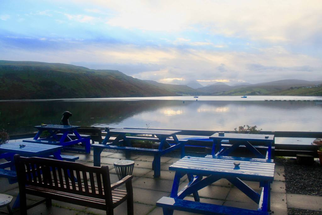 Blue picnic tables in front of a loch at dawn