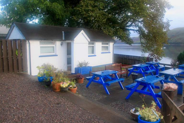 Small white cottage with blue picnic tables in front