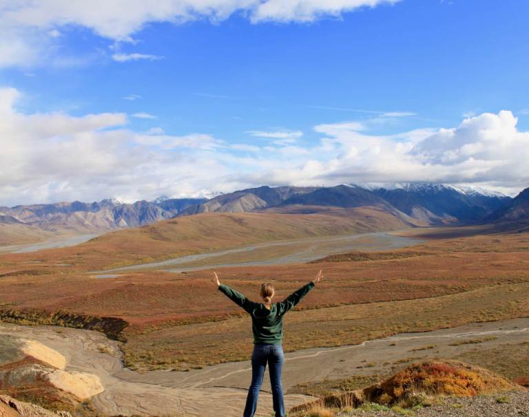 Gwen with arms spread wide in front of Polychrome Pass in Denali National Park