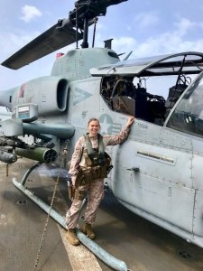 Ellen in military fatigues standing beside a helicopter