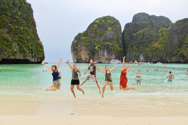 Five people jumping for joy in front of the karst formations and beautiful water of Maya Bay