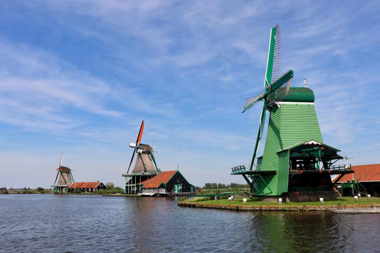 Three colorful windmills along the water in Zaanse Schans