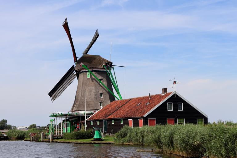 Windmill with red roofed building beside