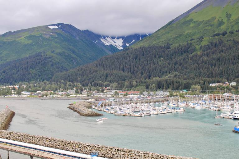 Cloudy view of the marina and town of Seward, Alaska. Don't forget to add a waterproof jacket to your Alaska packing list!