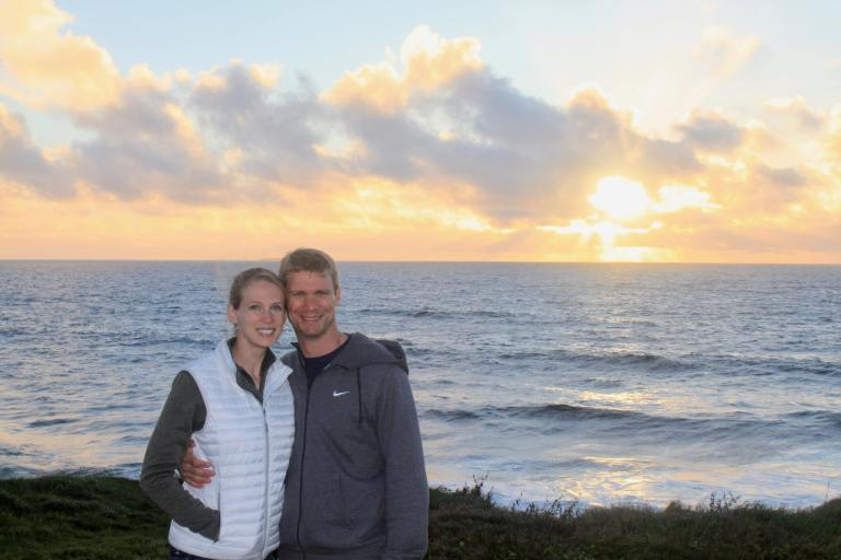 M and Gwen in front of the ocean and sunset