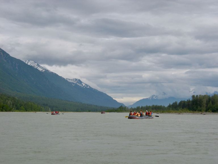 Three rafts with rafters floating down a river with mountains behind