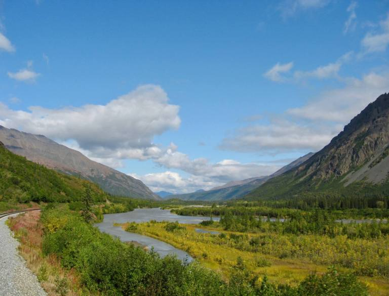 Glacial valley with river, mountains, and train tracks