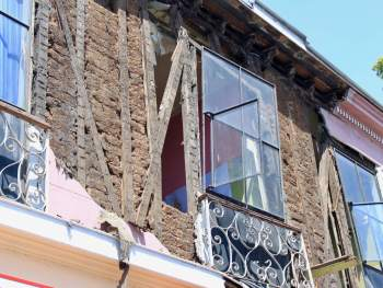 Broken window and brick building missing plaster after earthquake