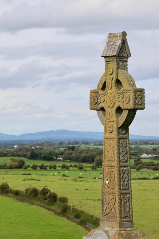 Stone Celtic cross grave marker with countryside beyond