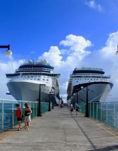 Two cruise ships docked at a cement dock