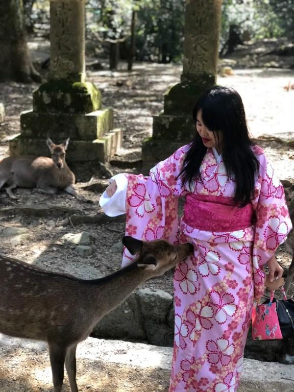 Erica in a pink kimono greeting a deer in Nara