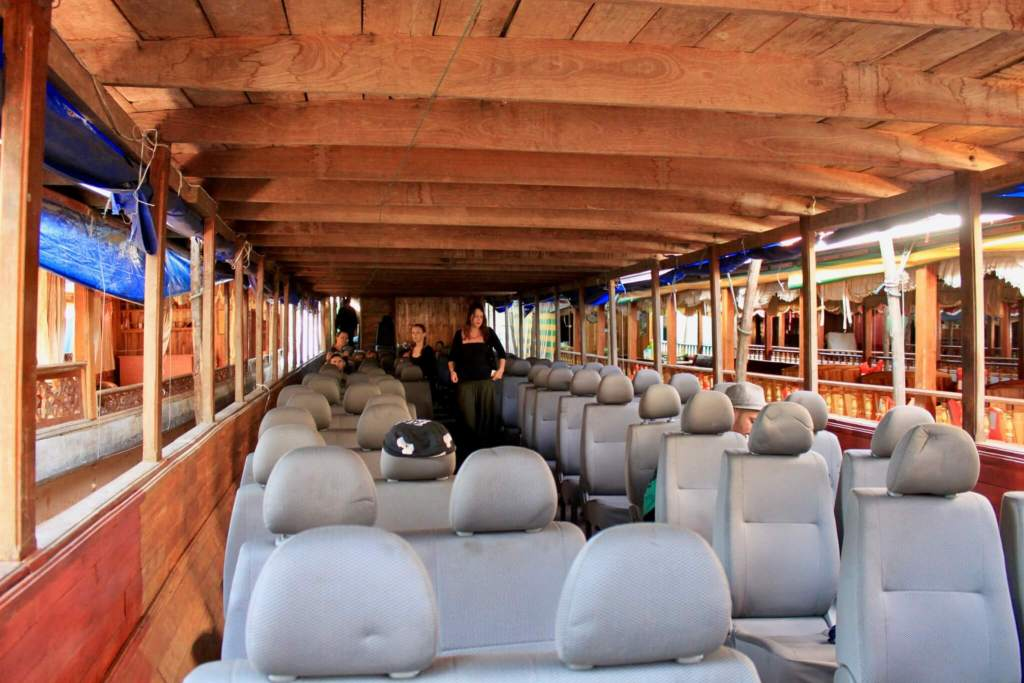 Interior of the longboat filled with rows of gray automobile seats. They're much more comfortable for a Mekong River cruise in Laos than the hard wooden benches of yesteryear!