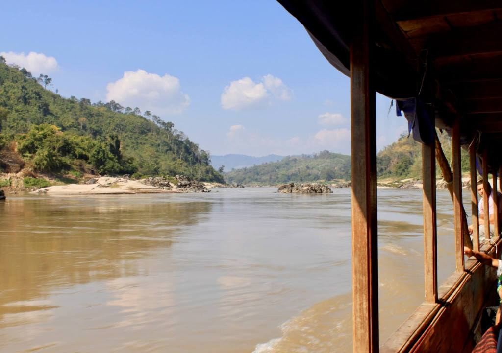 View of the river and green hillsides through the open longboat window