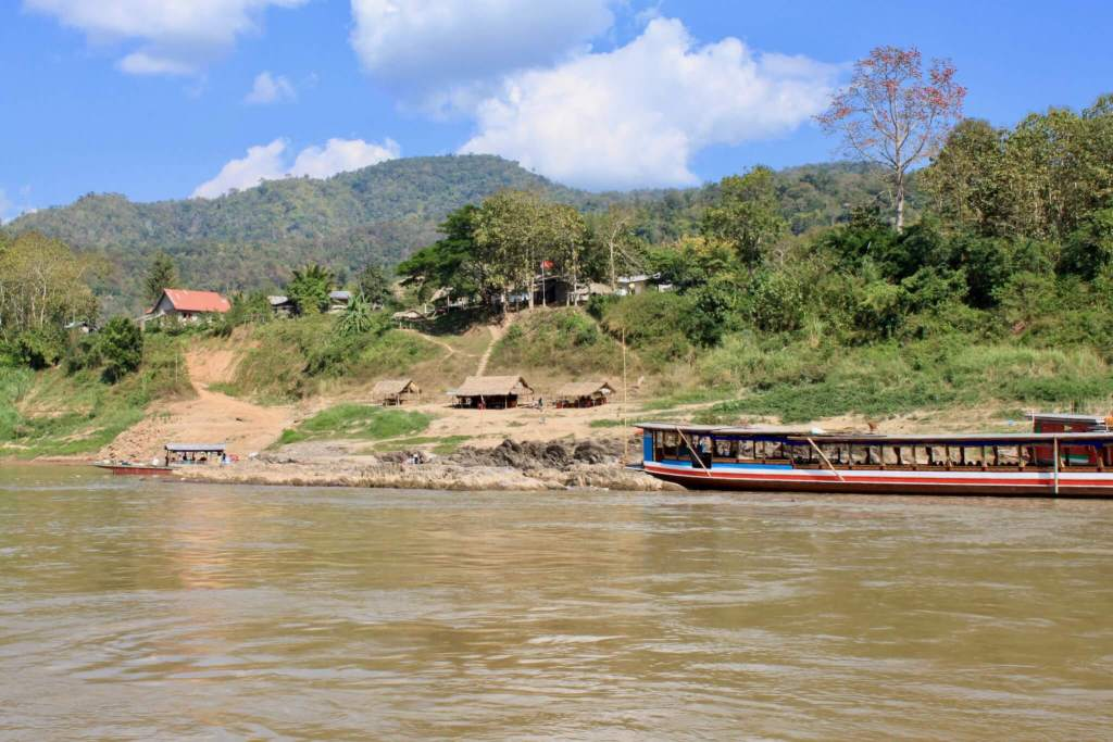 Another longboat docked beside a village perched on a green hillside. Just some of the beautiful scenery on a Mekong River cruise in Laos!