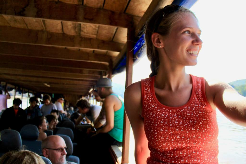 Gwen sitting in the window of the longboat and smiling out at the scenery - loving life on a Mekong River cruise in Laos!