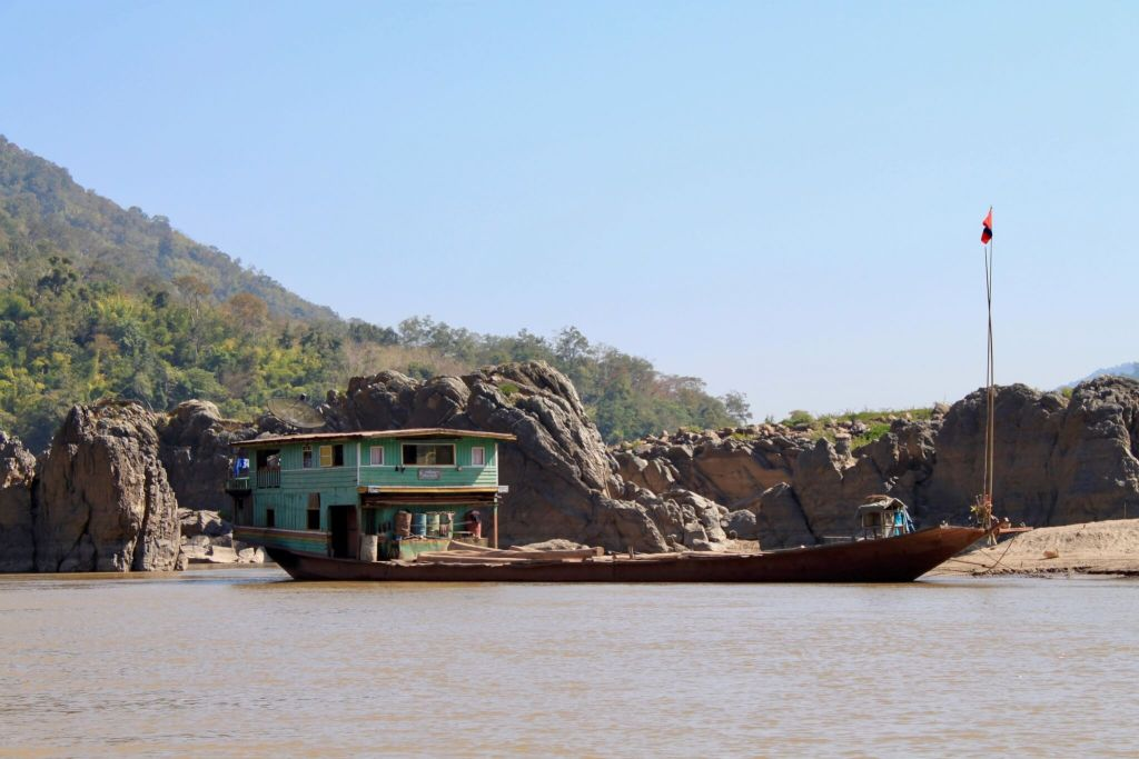 Two-story house perched on the rear of a long, low-sitting metal boat