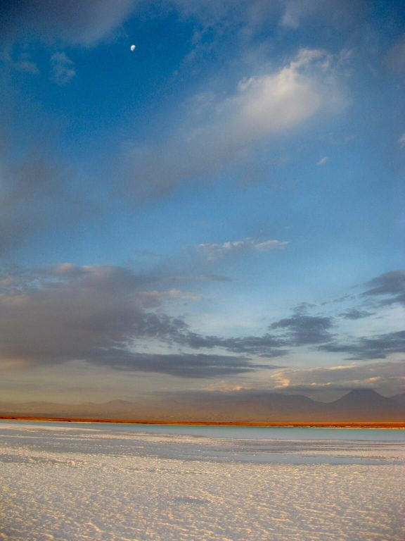 half-moon above the salt flats of the Salar de Atacama
