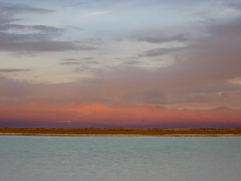 Pink-hued mountains and teal-colored water