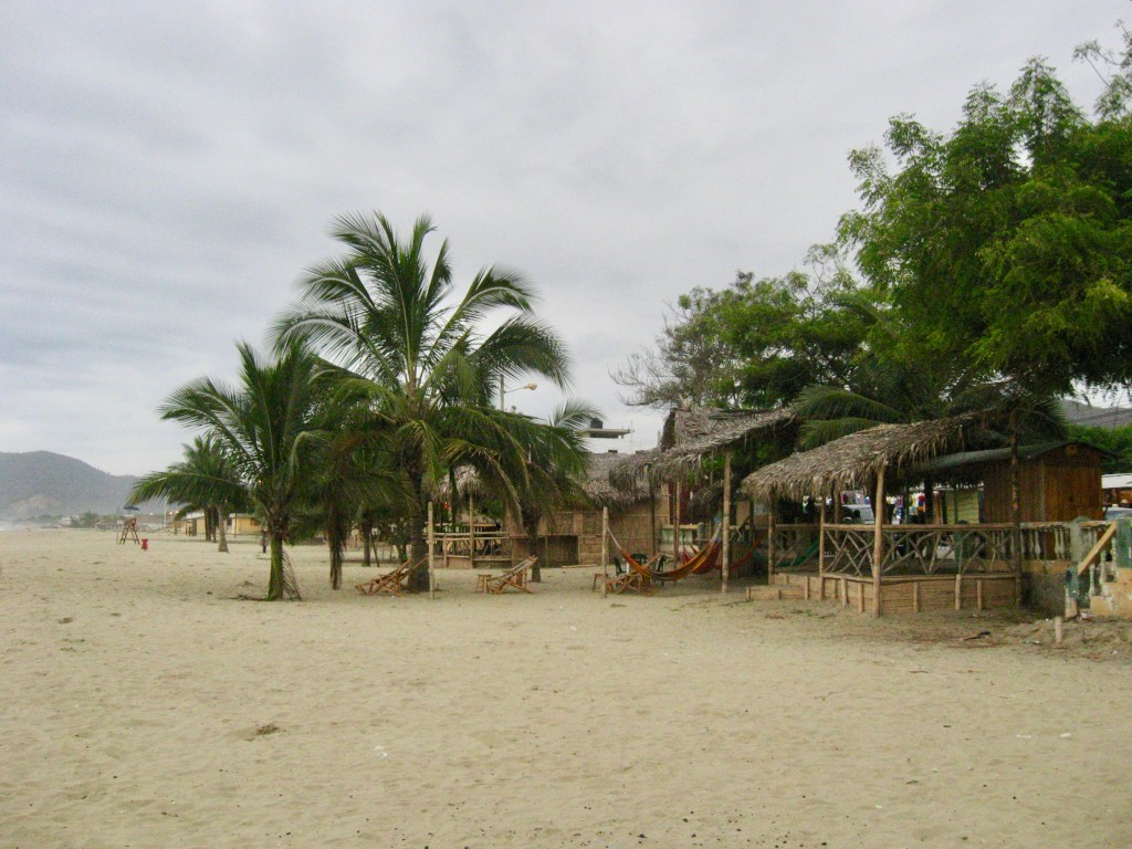 Thatch-roofed beach bars in the sand of Puerto Lopez