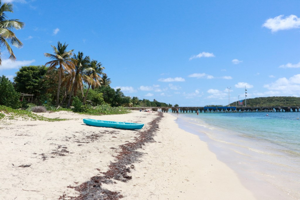 Blue kayak on Esperanza Beach, Vieques, with pier in background