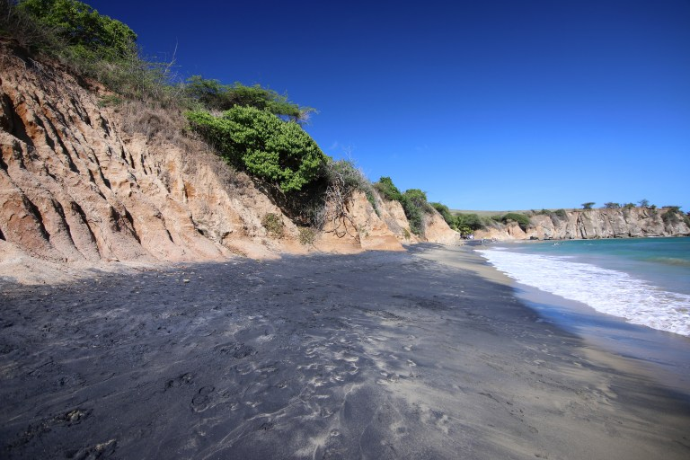 View of Playa Negra with black sand and tan-colored cliffs