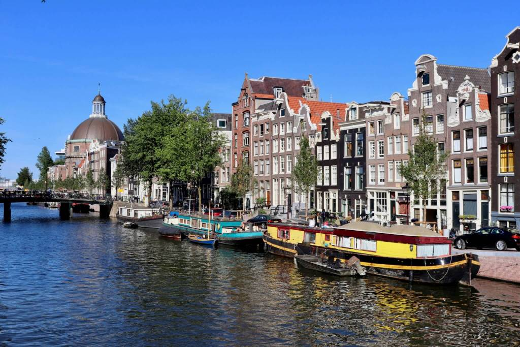 Colorful houseboats in front of row homes in Amsterdam