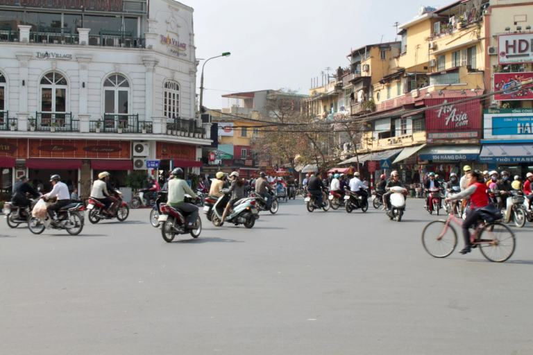 Motorbikes and bicycles traveling in all directions through an open square in Hanoi, Vietnam