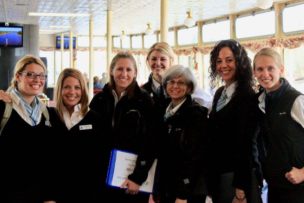 Seven female tour directors smiling in uniform