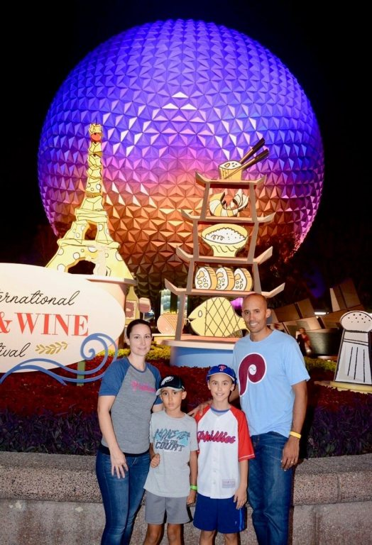 Natalie and her family in front of the Epcot ball at night