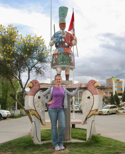 Gwen standing in front of a statue of parrots and man in native dress