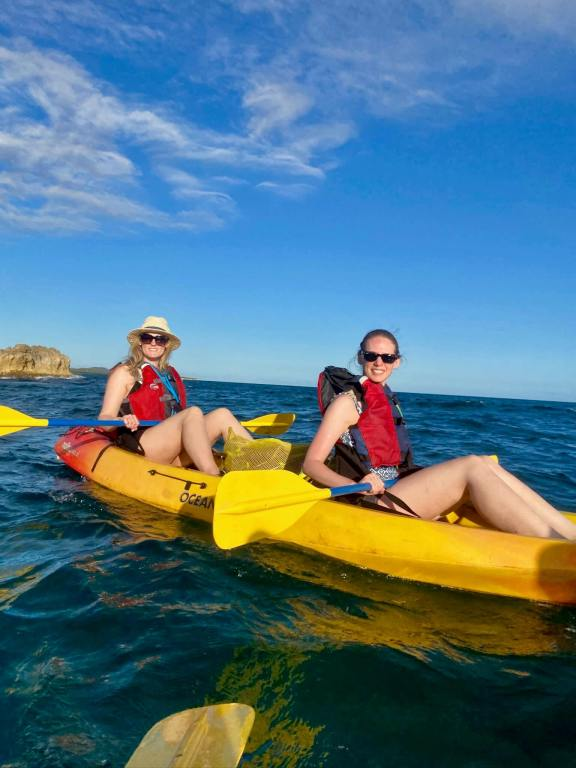 Brooke and Gwen smiling on a yellow kayak in the ocean