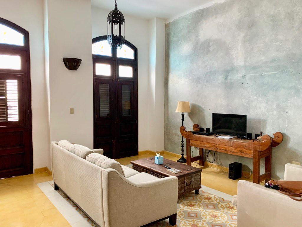 Living area of hotel suite with sofa and TV