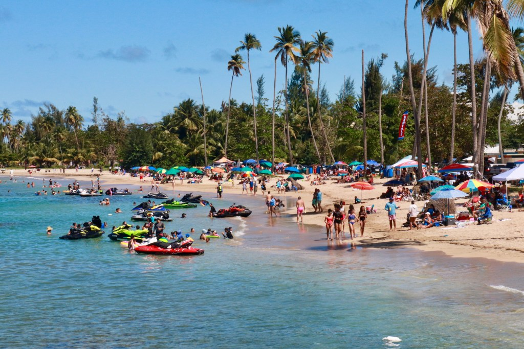 Beachgoers flanked by palm trees and umbrellas with jet skis in the teal water