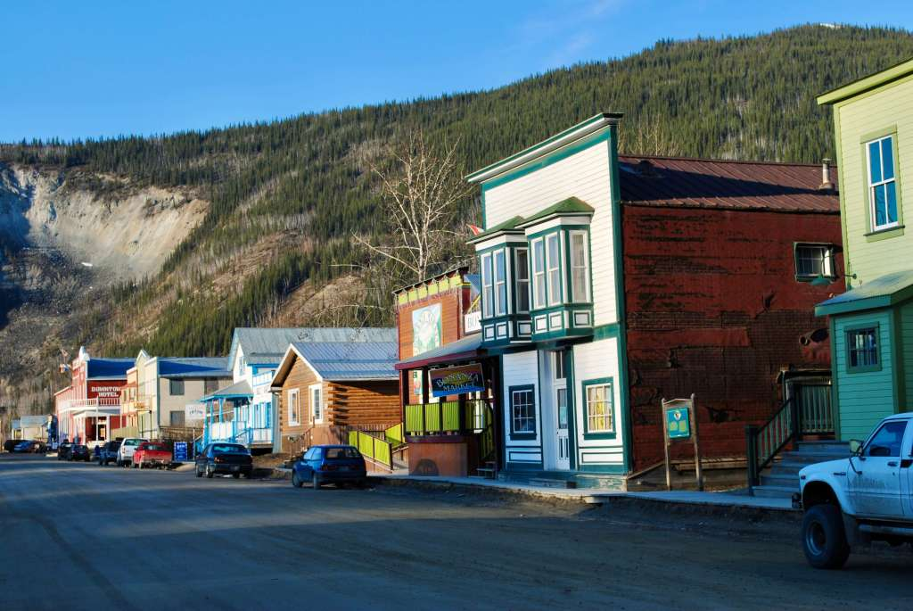 Colorful buildings of Dawson City with hillside beyond