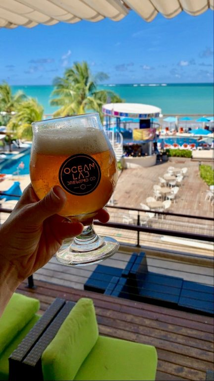 Glass of Ocean Lab beer being held in front of a view of the beach club
