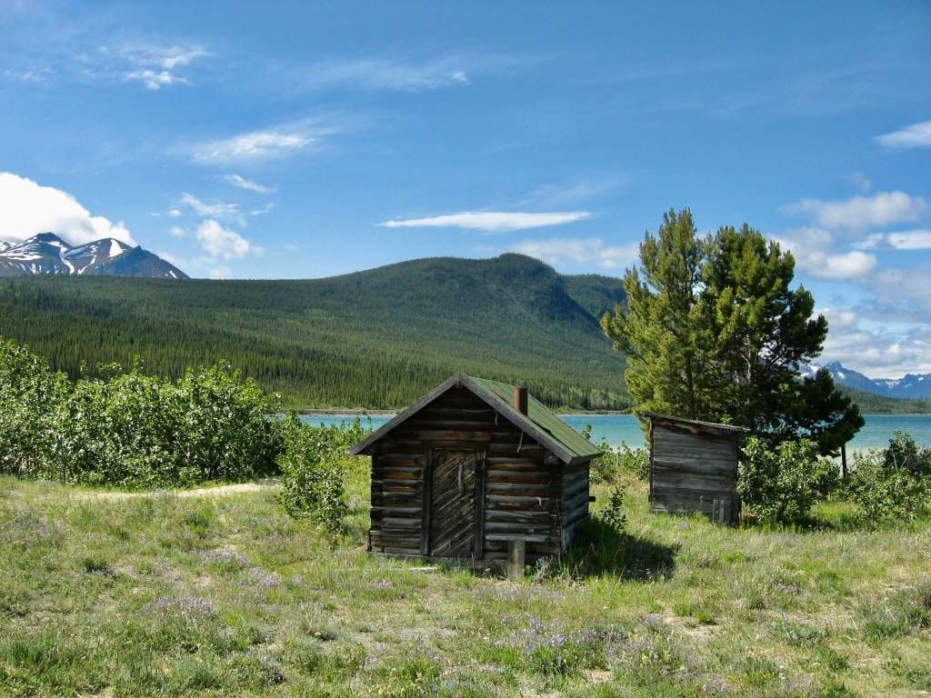 Small log cabin with mountains beyond outside Carcross, Yukon