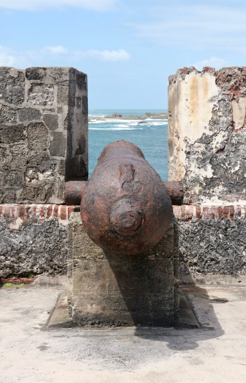 Cannon pointing through the battlements toward the ocean