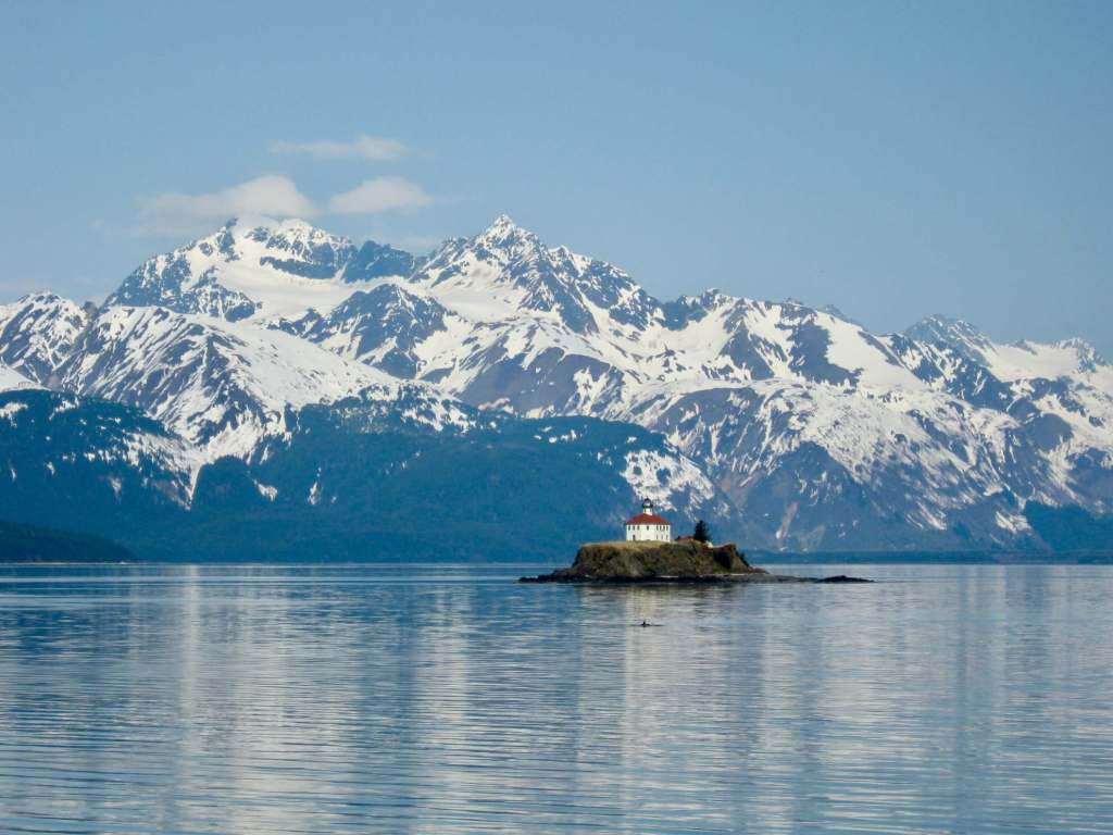 Lighthouse in front of snow-capped mountains