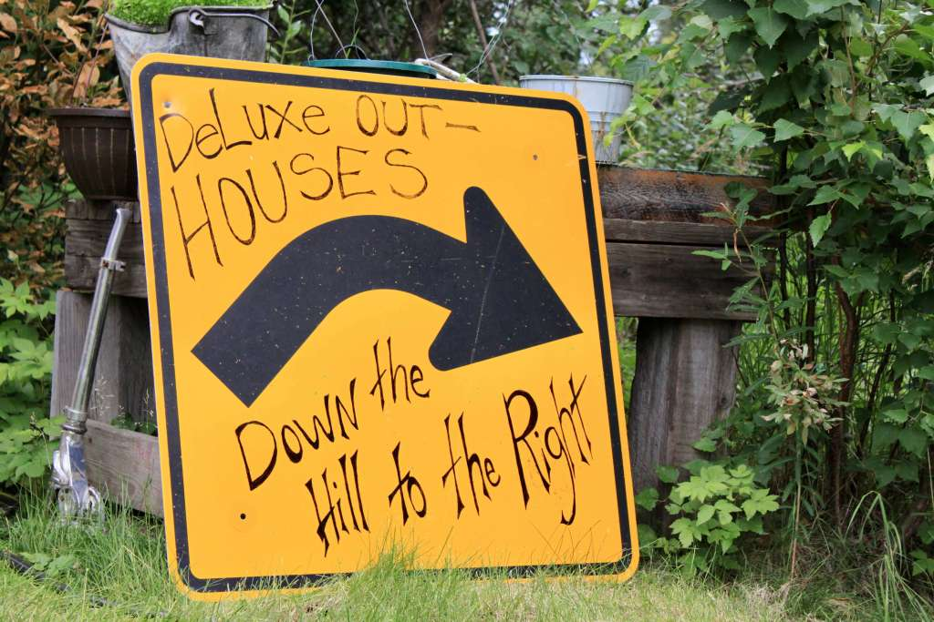 """Road sign with hand-written letters saying """"Deluxe outhouses down the hill to the right"""""""