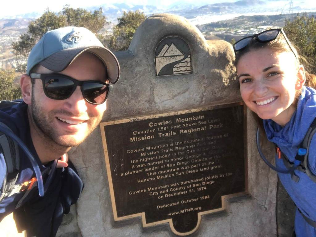 Chad and Charlotte in front of a Cowles Mountain plaque - doing another of the best hikes in San Diego!
