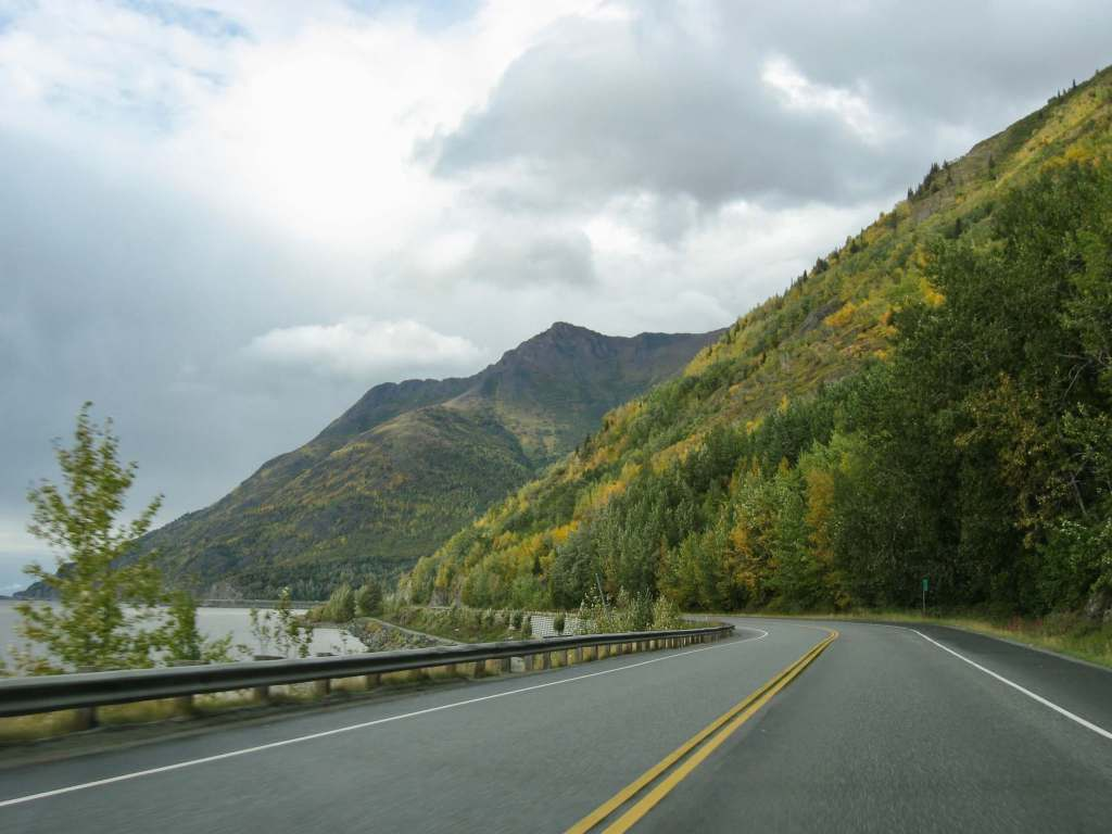 The Seward Highway with the Turnagain Arm on the left and mountains on the right.