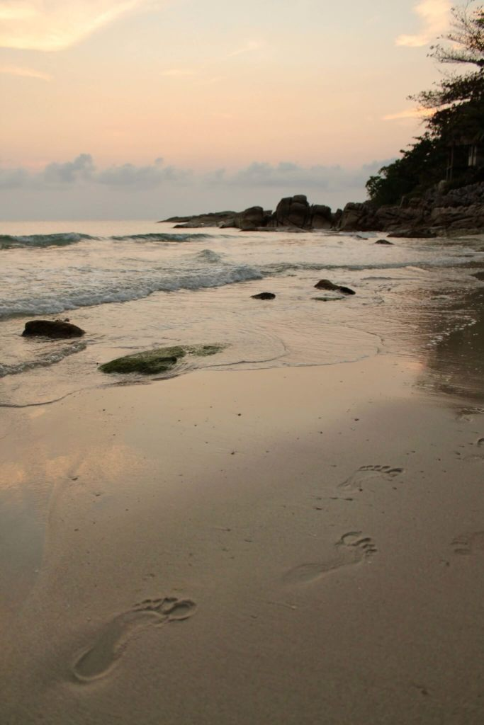 Dusk on the beach with footprints in the wet sand
