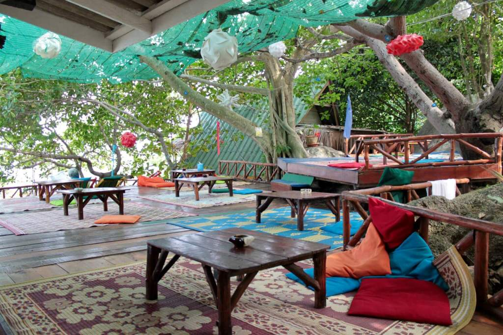 Lounge and restaurant area at Treehouse with low tables and colorful cushions