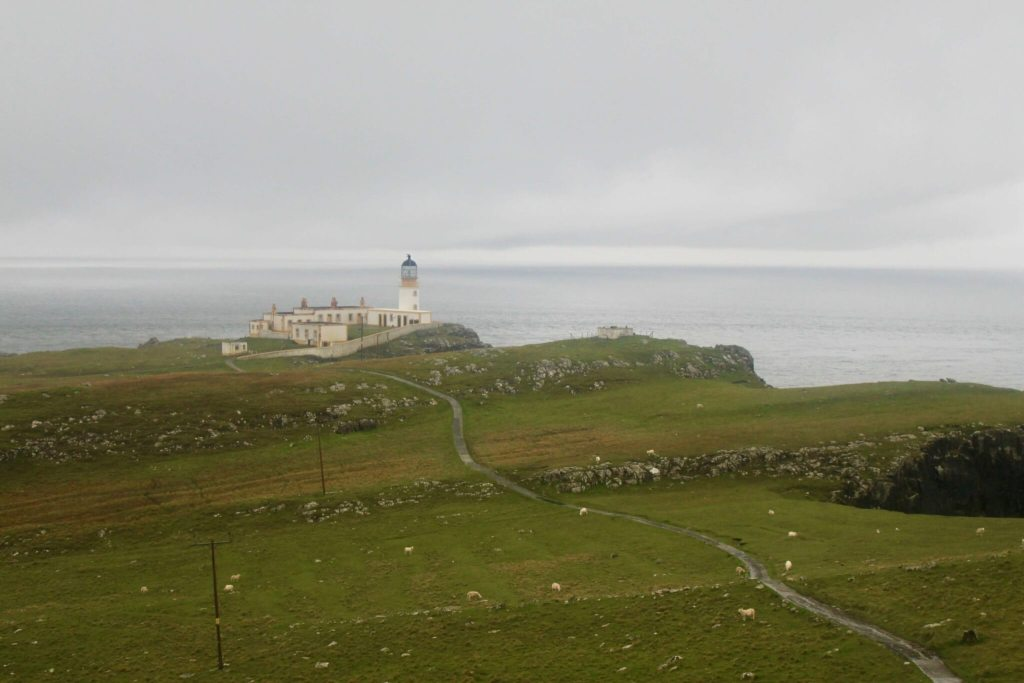 The Neist Point Lighthouse in the distance on a gray and gloomy day