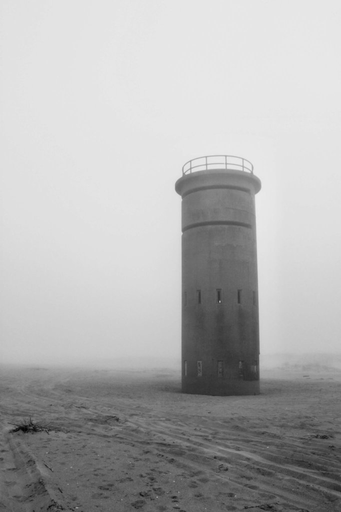 Black and white photo of a World War II watchtower in the sand