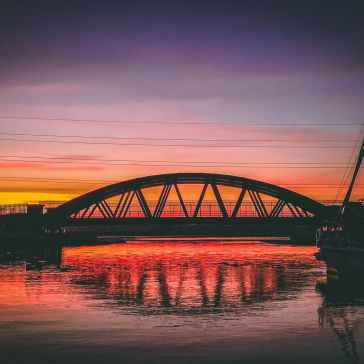 silhouette of bridge under orange sky