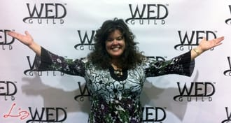 Wedding Entertainment Director® Elisabeth Scott Daley in front of the WED Guild® Step & Repeat.