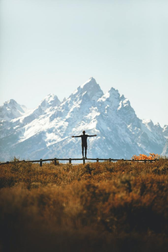 praising the world with mountains in the background