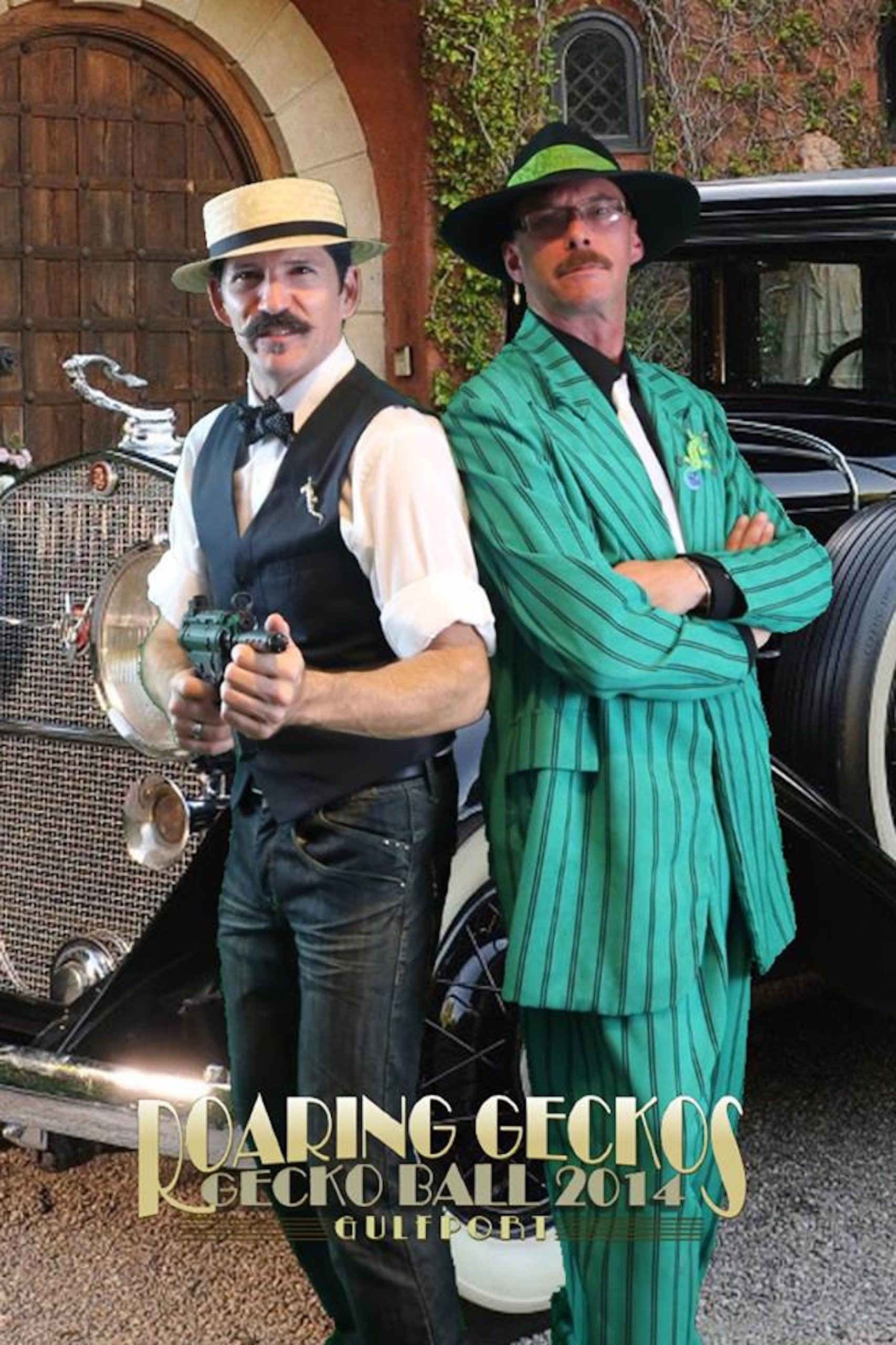Two men in 1920s gangster costumes, one with machine gun prop and one with green suit, smile at camera.