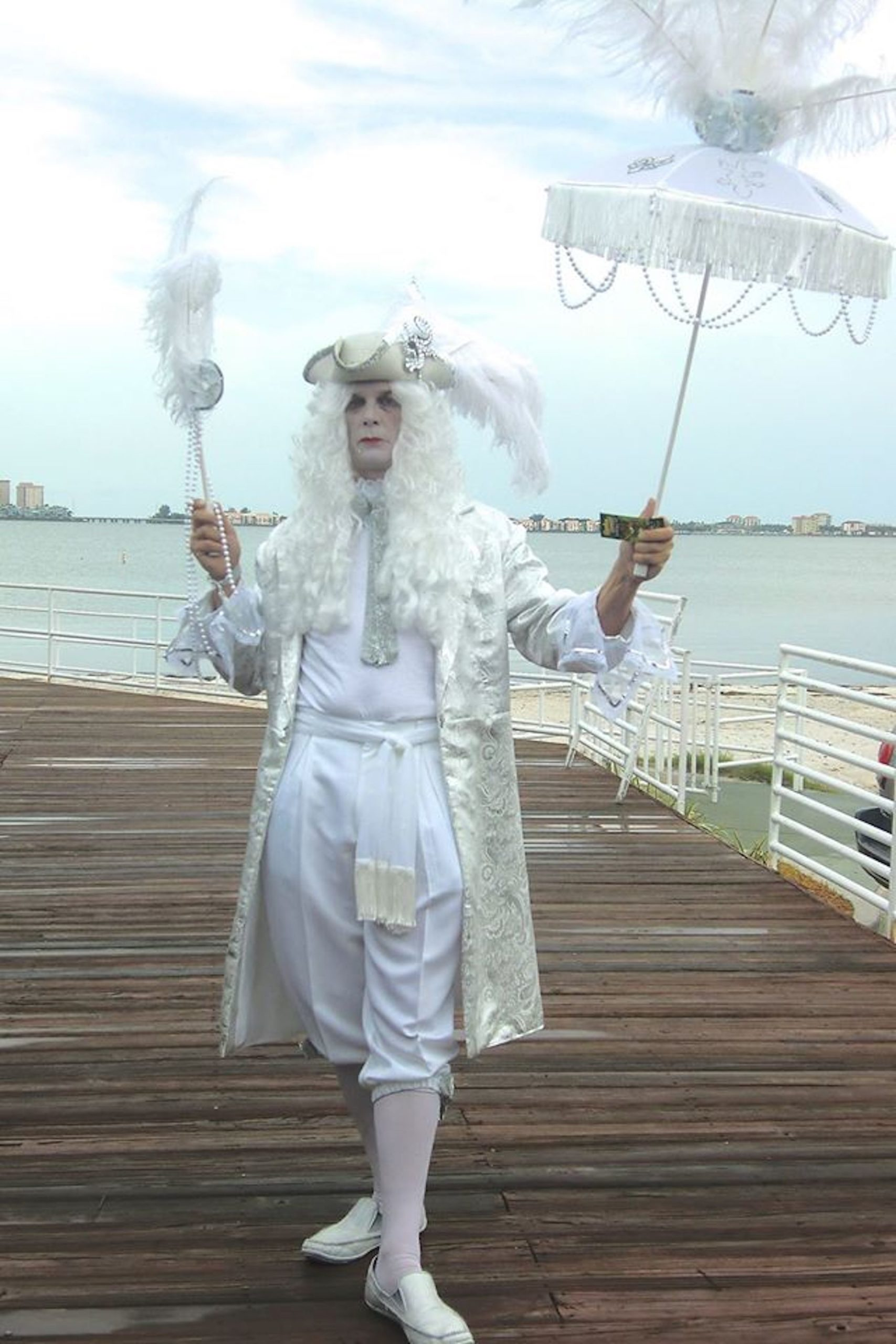 A man in an all-white 18th Century costume with white umbrella and long white wig in front of water.